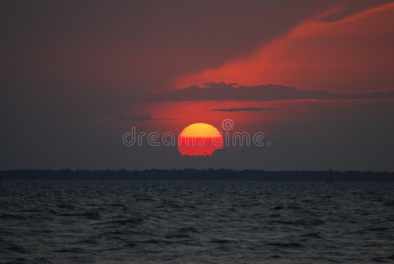 Красное солнце и красный заход солнца неба над океаном стоковое изображение