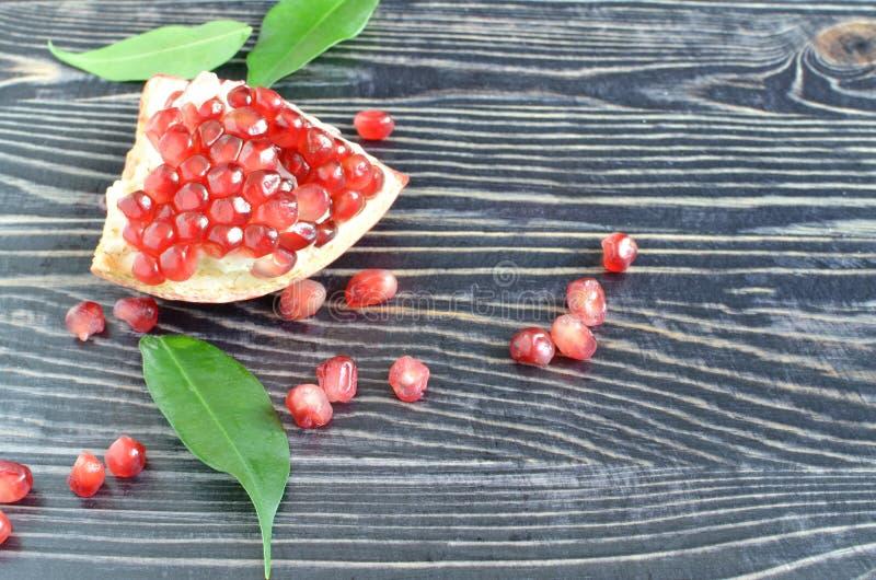 Красное сочное гранатовое дерево плодоовощ с красными семенами на черной деревянной предпосылке стоковое фото