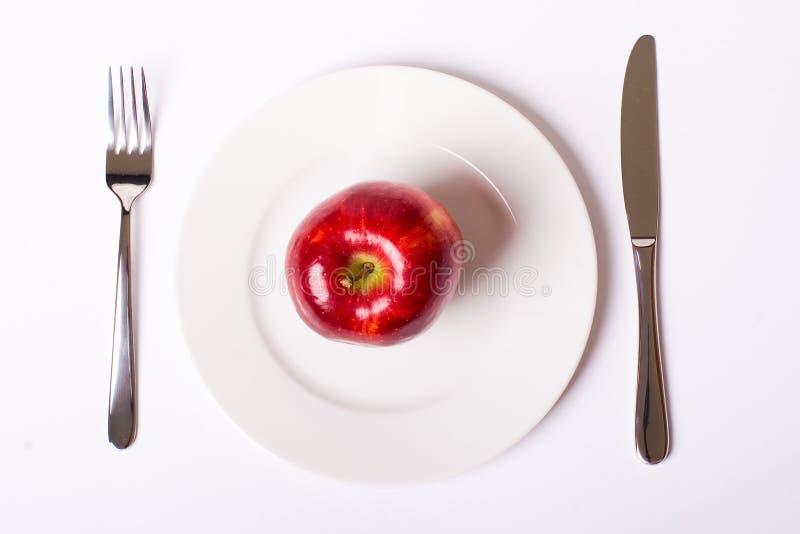 Красное яблоко на белой плите стоковые фотографии rf