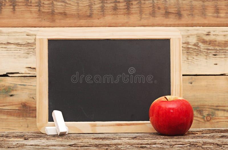 Красное яблоко на доске стоковые изображения rf
