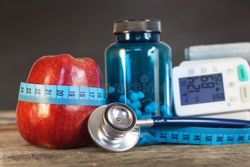 Красное яблоко с измеряя лентой для того чтобы измерить длину Обработка тучности и диабет, измерение кровяного давления стоковое изображение