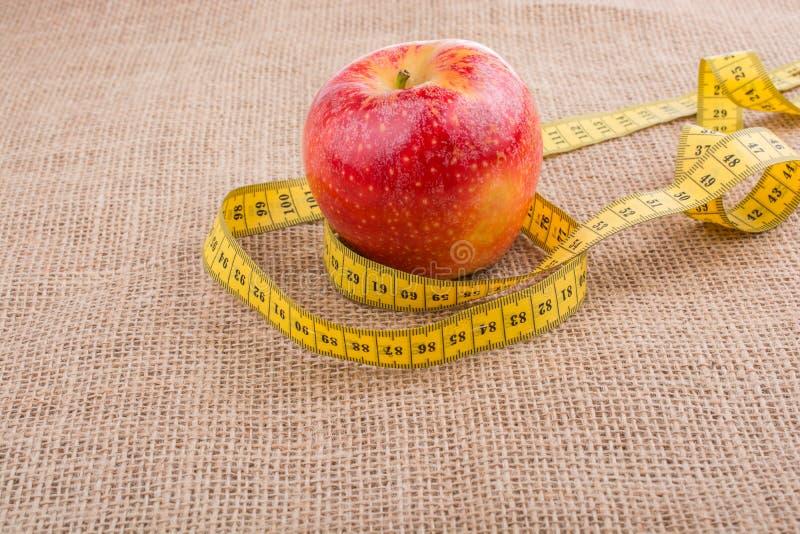 Красное яблоко с лентой измерения на ей стоковые изображения