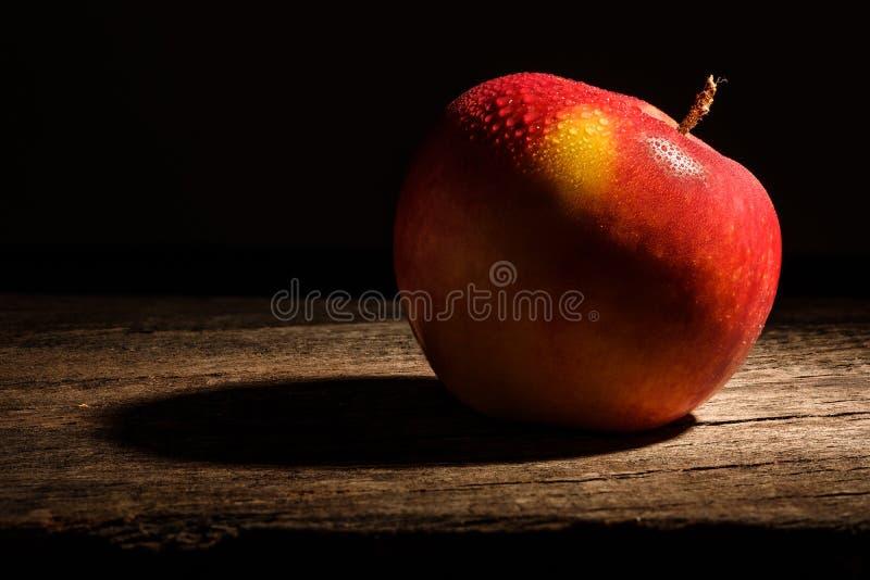 Красное яблоко с падениями воды на деревенской древесине стоковое изображение