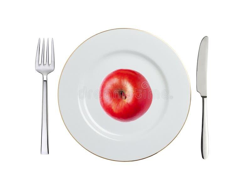 Красное яблоко на белых плите, ложке и вилке изолированной на белизне стоковое фото