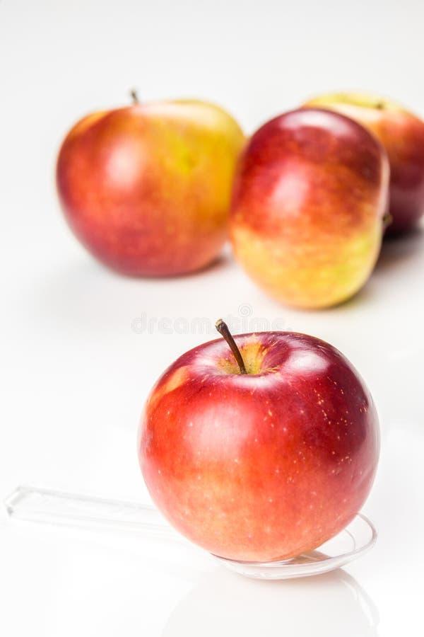 Красное яблоко на просвечивающей ложке медицины на таблице стоковое изображение
