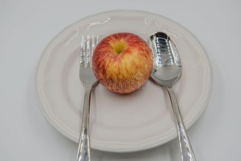 Красное яблоко на плите и ложке, вилке на белой предпосылке стоковые изображения
