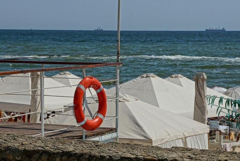 Красное lifebuoy на загородке белых беседок ткани на пляже около моря развевает стоковое фото rf