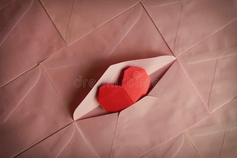 Красное origami бумаги сердца в розовой предпосылке конверта стоковое фото