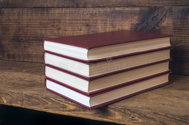 4 Красной книги штабелированной на деревянной полке стоковое фото