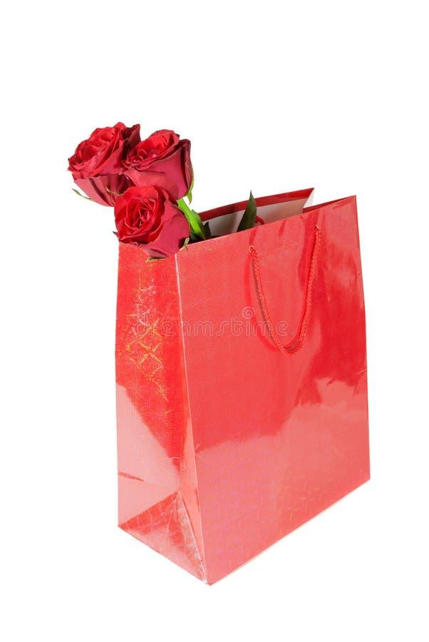 3 красной розы в красном подарке кладут в мешки на белой предпосылке стоковые изображения rf