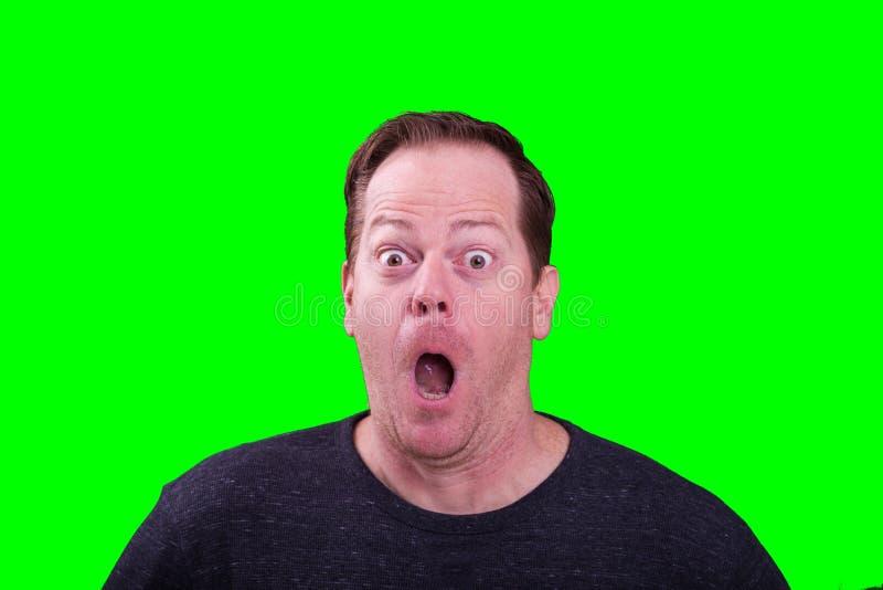 Красной с волосами мужчина достигший возраста серединой удивил забавное выражение лица на яркой ой-зелен предпосылке экрана стоковое изображение