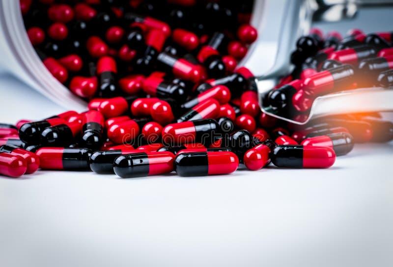 Красно-черные антибиотические пилюльки капсулы разливают из белых пластичных контейнера бутылки и подноса лекарства Фармацевтичес стоковое изображение rf