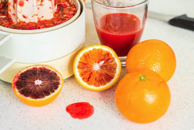 Красные апельсины, питье и juicer на таблице стоковые фото