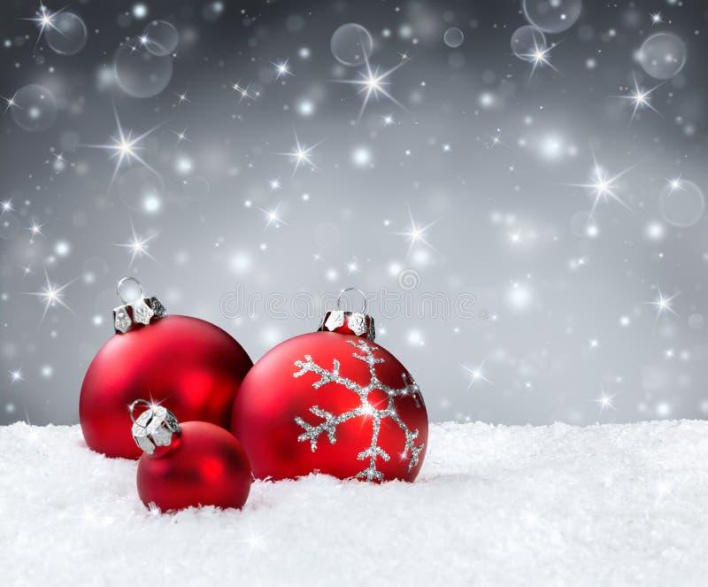 Красные безделушки на снеге стоковая фотография