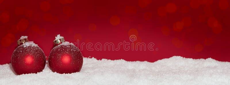 Красные безделушки рождества в снеге стоковые фотографии rf