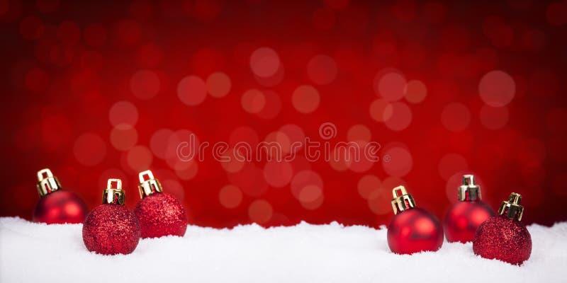 Красные безделушки рождества на снеге с красной предпосылкой стоковая фотография rf