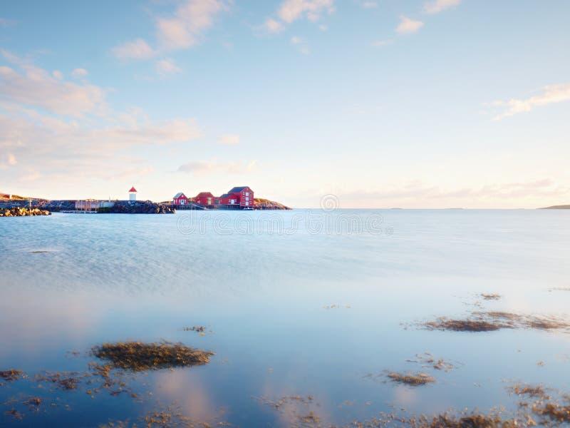 Красные белые здания и маяк в малом порте, береговой линии холодного Северного моря, Норвегии стоковое изображение