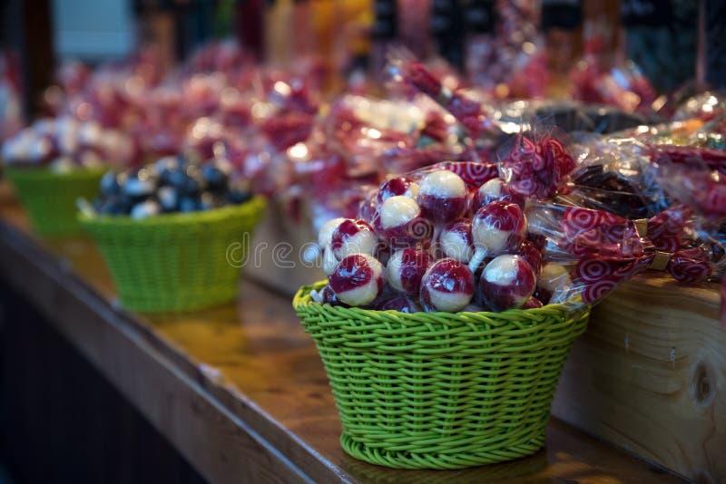 Красные белые леденцы на палочке в зеленых корзинах в магазине конфеты на chr стоковая фотография rf