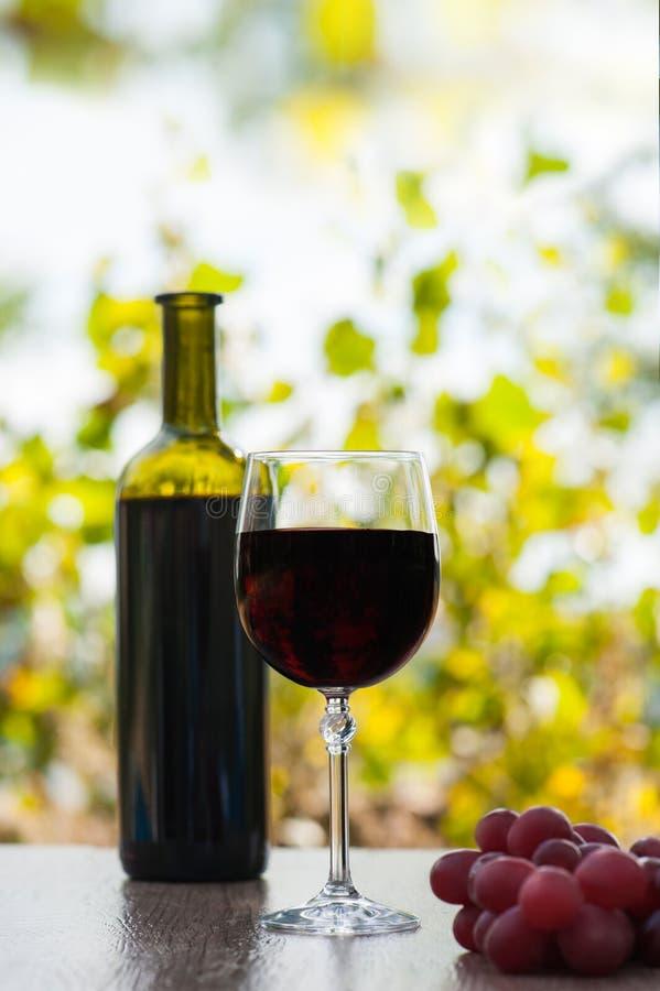 Красные бокал и бутылка на деревянной поверхности с красными виноградинами стоковое фото