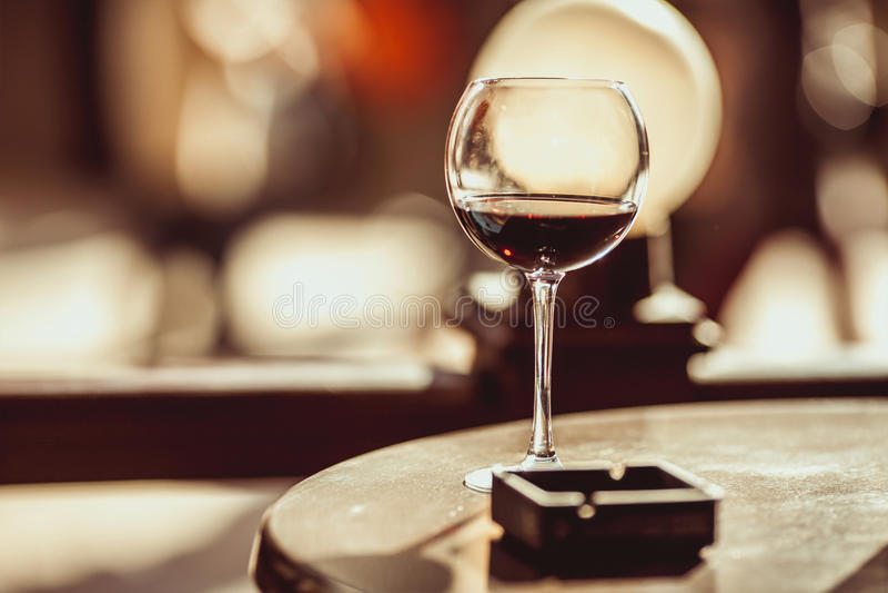 Красные бокал и ashtray на таблице в кафе стоковые фотографии rf