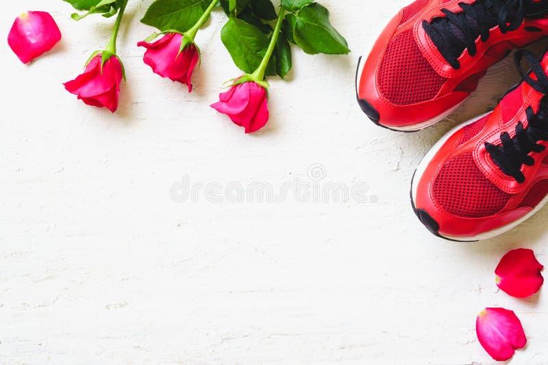 Красные ботинки и красные розы спорта на белой деревянной предпосылке, Valen стоковое фото rf