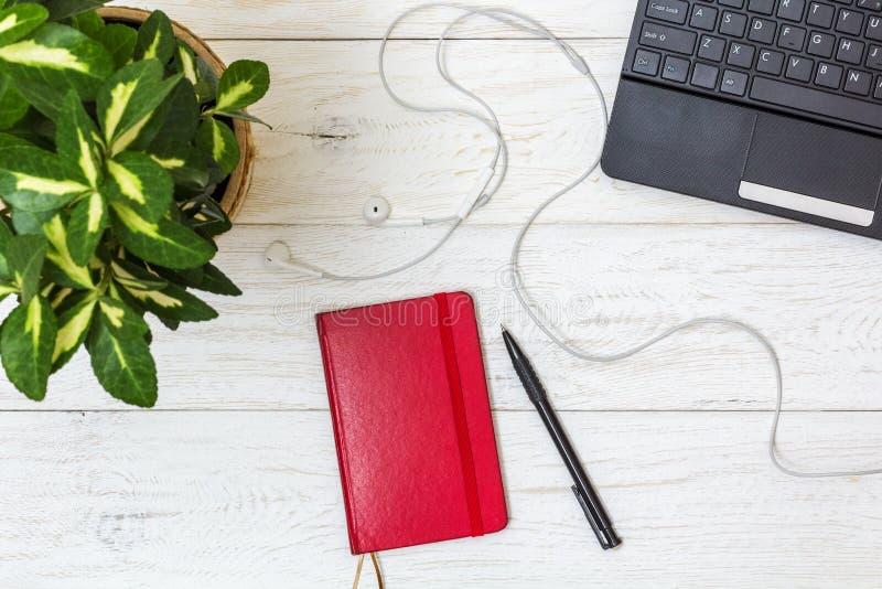 Красные блокнот и компьтер-книжка на белых досках стоковая фотография