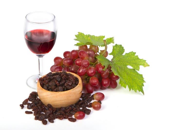 Красные виноградины и изюминки с бокалом вина стоковое изображение rf