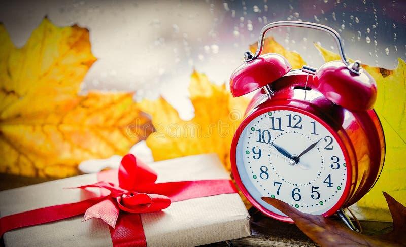 Красные винтажные будильник и подарочная коробка с кленовыми листами стоковое фото rf