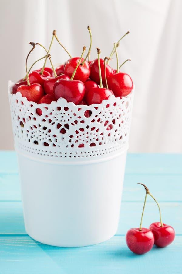 Красные вишни в белом ведре стоковые изображения