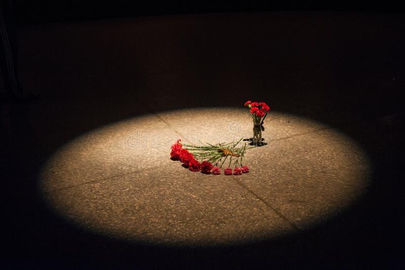 Красные гвоздики лежат на слябе гранита памятника к солдатам стоковое фото