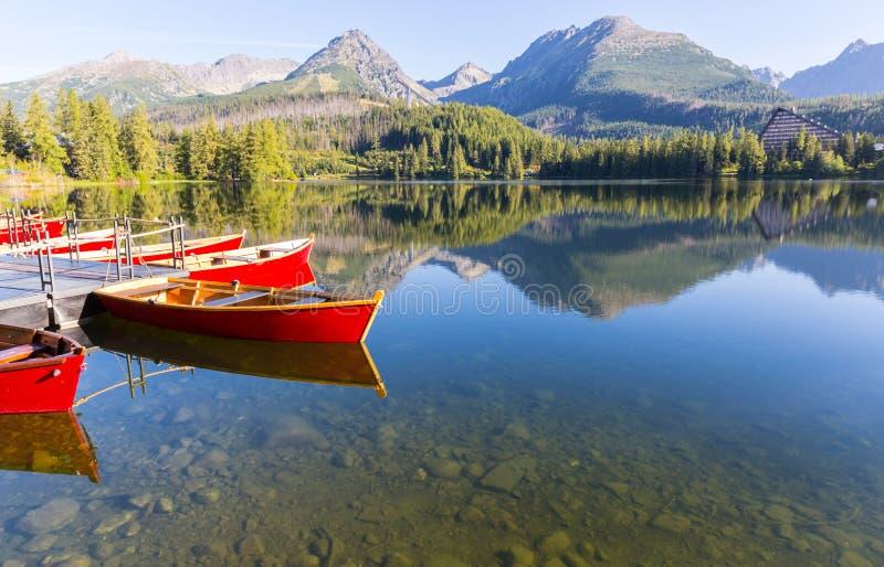 красные деревянные шлюпки на поверхности воды озера стоковое изображение