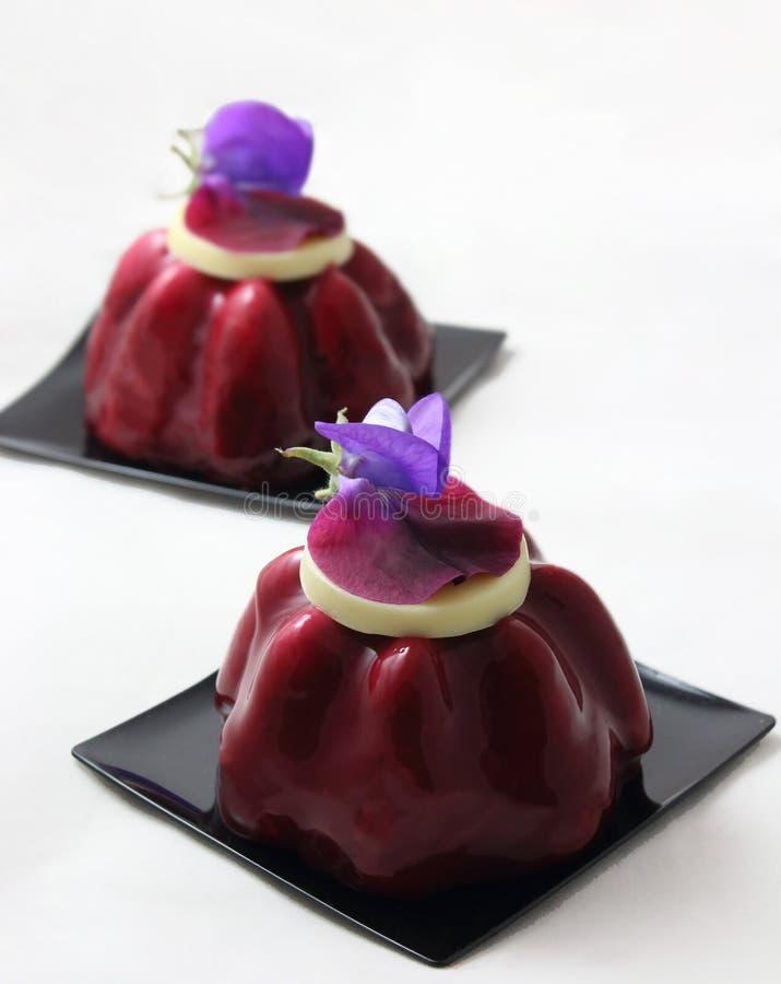 Красные десерты ягоды с белым шоколадом и съестными цветками гороха стоковое фото rf