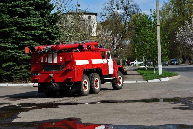 Красные езды пожарной машины вдоль дороги от гаража к аварийному вызову, заднему взгляду с отражением в лужицах стоковое изображение rf