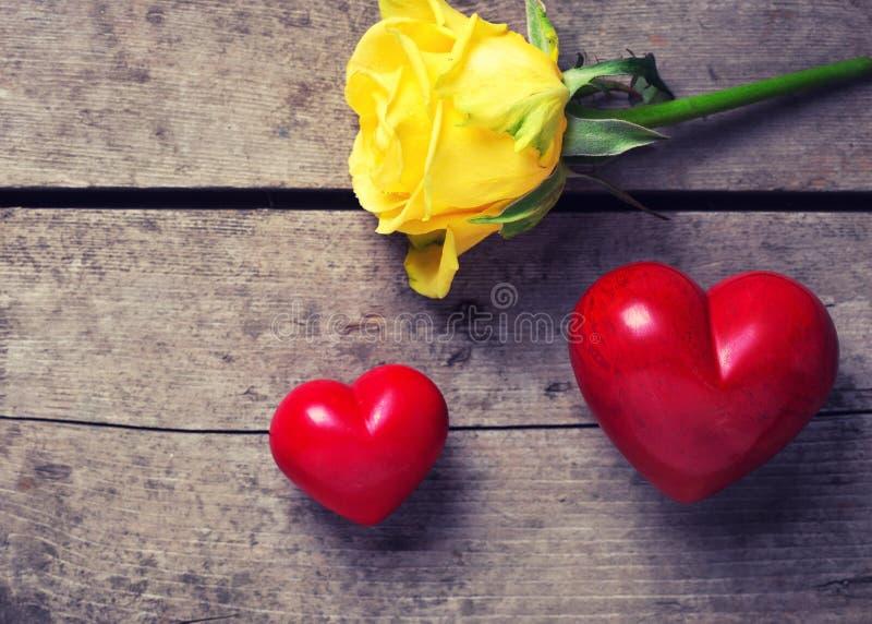 Красные декоративные сердца и розовый цветок на постаретом деревянном backgroun стоковые изображения rf