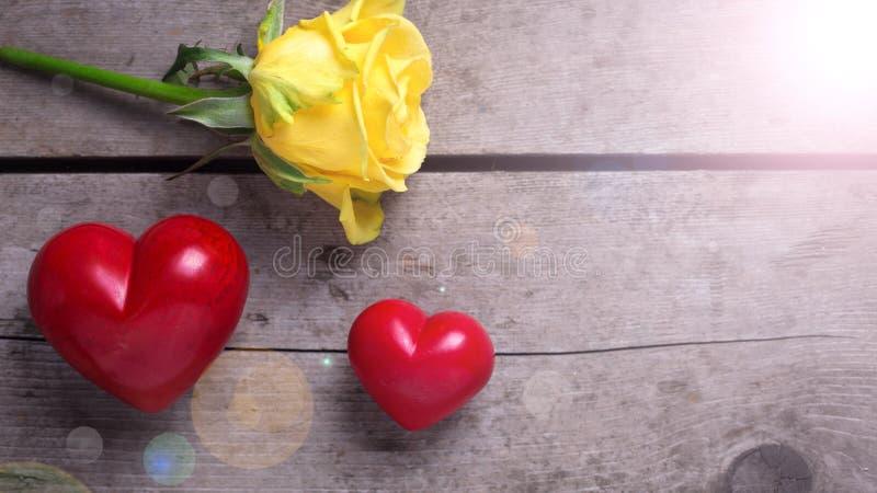 Красные декоративные сердца и розовый цветок на постаретом деревянном backgroun стоковые изображения