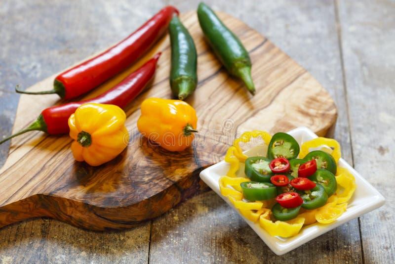 Красные, зеленые и желтые горячие перцы на деревянной доске стоковая фотография rf