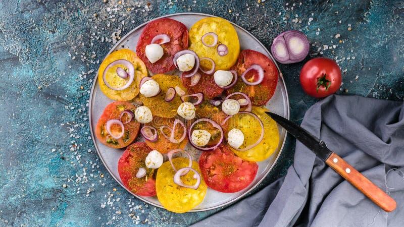 Красные знамени еды вкусные и желтые томаты с луками, сыром моццареллы, солью и специями на круглой плите стоковое изображение