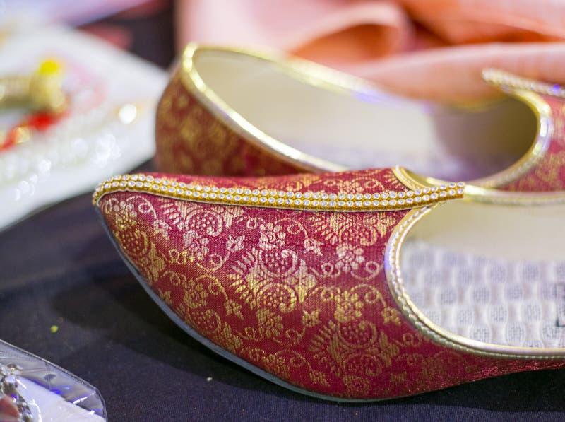 Красные индийские ботинки свадьбы или этнические ботинки обыкновенно известные как mojdi или mojri стоковые фото