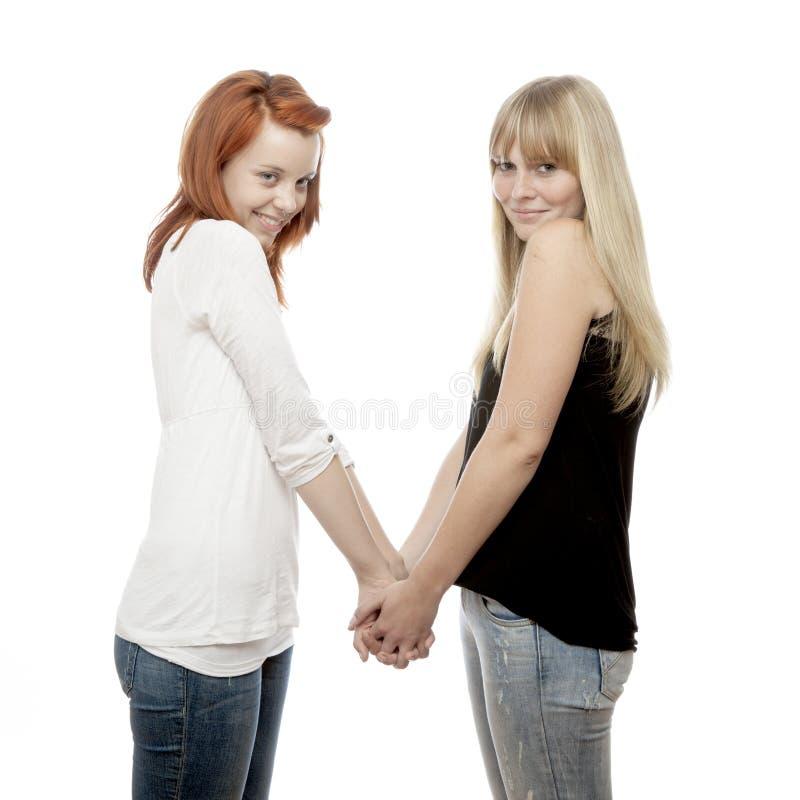 красные и белокурые с волосами девушки держа руки стоковое фото rf