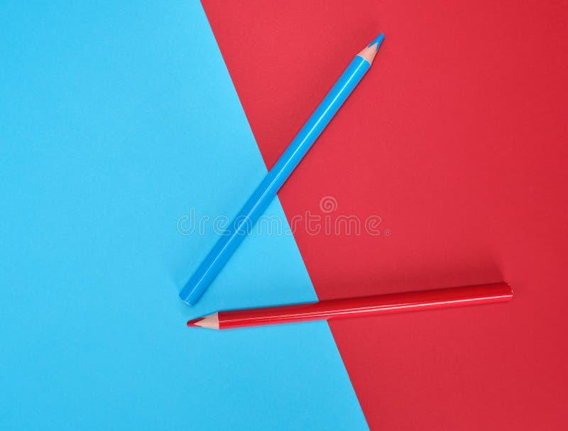 Красные и голубые деревянные карандаши на предпосылке цвета абстрактной стоковые фото