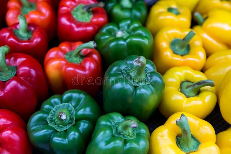 Красные и желтые и зеленые сладкие перцы Перцы кучи 3 сладкие на деревянной предпосылке, варя салат овоща стоковые фото