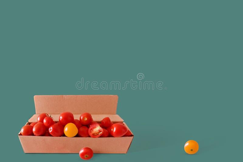 Красные и желтые свежие томаты вишни в картонной коробке на зеленой предпосылке Коллаж свежих овощей творческое изображение стоковое изображение rf