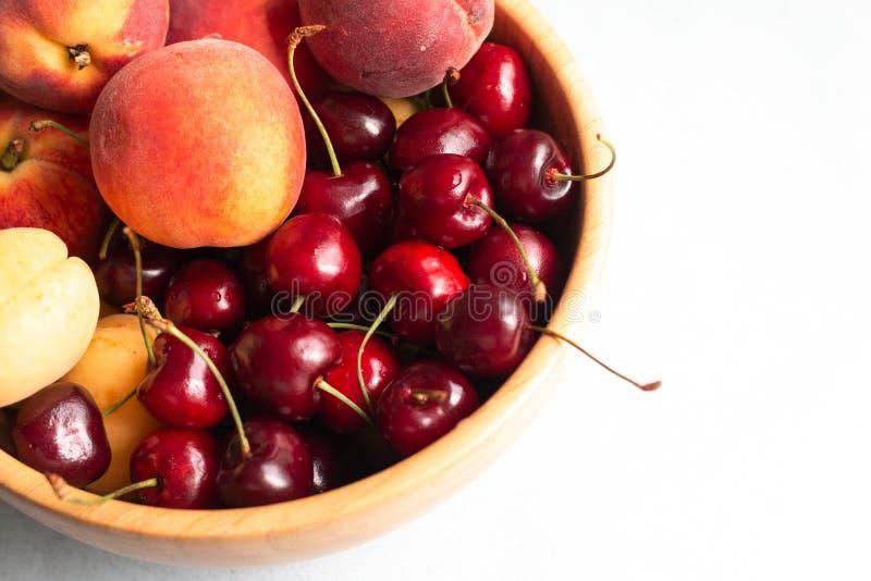 Красные и желтые ягоды и персики вишни смешанные на одной плите, еде лета свежей здоровой, изображении с космосом для текста стоковое изображение