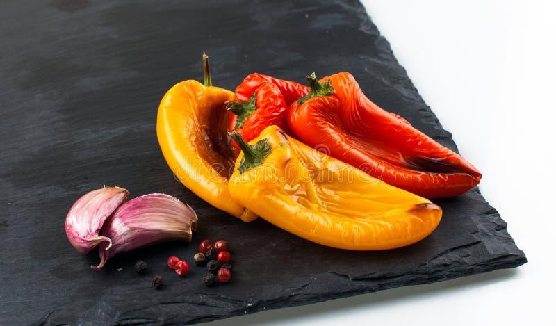 Красные и желтые перцы зажарили на оливковом масле гарнированном с чесноком стоковое фото