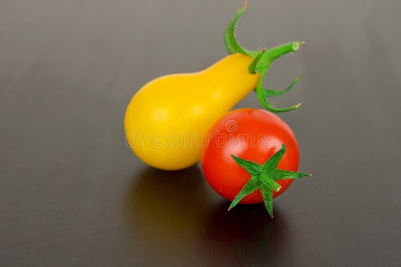 Красные и желтые томаты вишни на черной предпосылке стоковое изображение