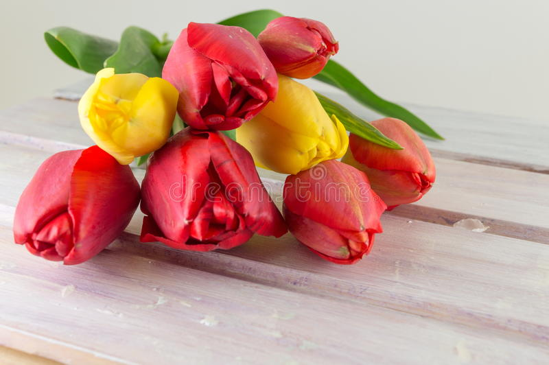 Красные и желтые тюльпаны на деревянном столе стоковая фотография