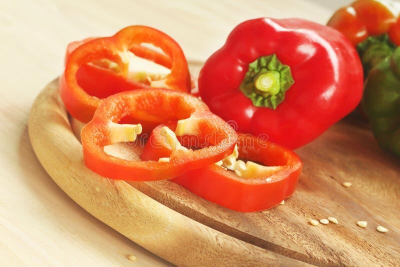Красные и зеленые болгарские перцы на деревянной разделочной доске стоковое фото rf