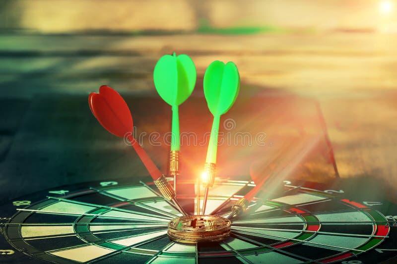 Красные и зеленые дротики шнуруют dartboard около bitcoin на dartboard стоковое фото rf