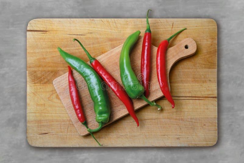Красные и зеленые перцы на деревянной доске стоковые фотографии rf
