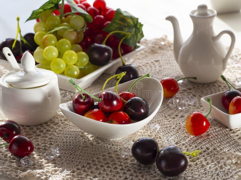 Красные и зеленые связки винограда, вишня, ложь яблока на белом блюде иллюстрация вектора